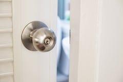 Bouton de porte inoxydable en gros plan, avec la porte ouverte légèrement Photo stock
