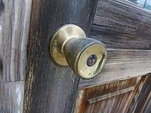 Bouton de porte sur la porte en bois brune Photographie stock libre de droits