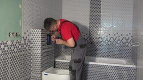 Bouton de rin?age de l'eau de toilette de b?ti d'homme de plombier dans la nouvelle salle de bains d'appartement banque de vidéos