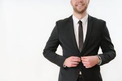 Bouton de sourire de côté de corps d'homme d'affaires vers le haut de son costume noir sur le blanc images stock