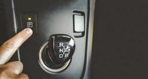 Bouton de vitesse de parc de presse de doigt de main sur des frais généraux intérieurs de voiture de transmission automatique  images libres de droits