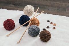 Bouton et boule de laine de fil sur le tapis Photos stock