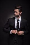 Boutonnage élégant de costume de jeune homme, regardant en longueur Image libre de droits