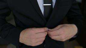 Boutonnage d'une veste L'homme élégant dans une attache de costume se boutonne sur sa veste préparant pour sortir banque de vidéos