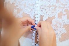 Boutonnage de la robe de mariage Photos libres de droits