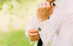 Boutonnage des manchettes Le marié porte des boutons de manchette Insertions d'homme d'affaires Photo libre de droits