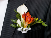 Boutonniere. Colorful wedding boutonniere on suit of groom stock images