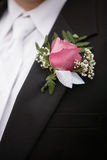 Boutonniere. Pink rose boutonniere flower on groom's wedding coat royalty free stock photos
