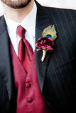 Boutonniere. A red boutonniere corsage with a peacock feather design Royalty Free Stock Photography