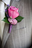 Boutonniere. Pink rose boutonniere pinned to a grooms jacket royalty free stock photo