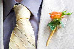 Boutonniere. Orange Rose Wedding Boutonniere On Suit of Groom Royalty Free Stock Photography
