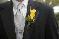 Boutonniere. Yellow calla lily wedding boutonniere on suit of groom royalty free stock photo