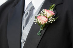 Boutonniere. Pink rose wedding boutonniere on suit of groom royalty free stock photography