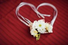 Boutonniere av vita rosor och tusenskönor för brudgummen Royaltyfri Fotografi