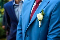 Boutonniere bleu de mariage sur la veste du ` s de marié Images stock