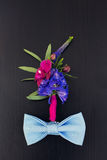 Boutonniere and bowtie on a wooden table. Colorful boutonniere and  blue bowtie  on a wooden table Stock Photos