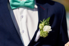 Boutonniere branco do casamento em Groom& x27; revestimento de s imagens de stock