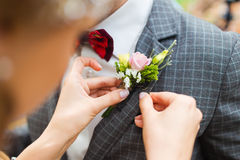 Boutonniere. Bride adjusting grooms boutonniere closeup royalty free stock image