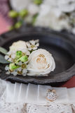 Boutonniere and bride`s garter on bride`s bouquet background. On bride bouquet background, white flowers lace Stock Photos