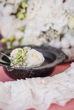 Boutonniere and bride`s garter on bride`s bouquet background. On bride bouquet background, white flowers lace Royalty Free Stock Image