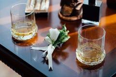 Boutonniere, cigarros y alcohol de la boda en una tabla de madera Imagen de archivo libre de regalías