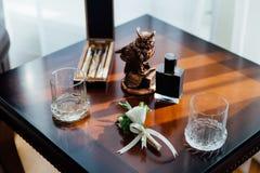 Boutonniere, cigarros y alcohol de la boda en una tabla de madera Imagenes de archivo