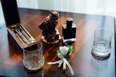 Boutonniere, cigarros y alcohol de la boda en una tabla de madera Fotografía de archivo libre de regalías