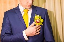 Boutonniere coloré de mariage sur le costume du marié Photos stock
