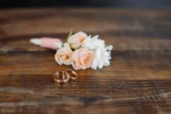 Boutonniere con gli anelli sul pavimento di legno immagini stock