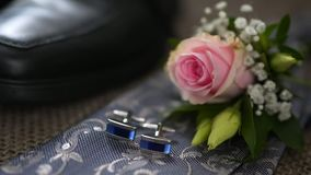 Boutonniere and cufflinks lie on the tie stock video footage