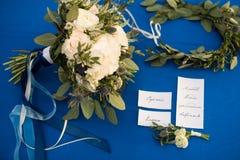 Boutonniere de Groom's e acessórios nupciais em um fundo azul fotos de stock