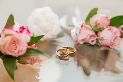 Boutonniere de la boda y anillos de bodas sobre el vidrio Imágenes de archivo libres de regalías