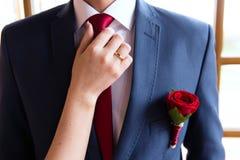 Boutonniere de mariage, main de jeunes mariées d'A sur le lien de marié Photos libres de droits
