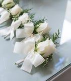 Boutonniere de roses blanches avec les garçons d'honneur blancs de ruban de noeud papillon sur g Photo stock