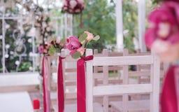 Boutonniere des fleurs fraîches sur un dos d'une chaise blanche image stock