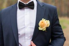 Boutonniere do casamento com a rosa do amarelo no terno do noivo Noivo no casaco azul, na camisa branca e no traje de cerimônia c foto de stock