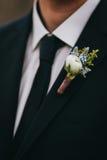 Boutonniere för vitros- och blåttblommor på groom& x27; s-svartdräkt w Royaltyfri Bild