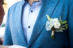Boutonniere groom in the pocket of a bridal blue jacket royalty free stock images