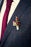 Boutonniere on groom's suit. Rose bush boutonniere on groom's grey suit Royalty Free Stock Photo