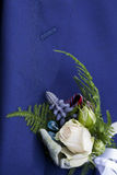 Boutonniere and lapel. Closeup of a groom's suited chest with buttonhole flowers. Selective focus and room for  text Stock Images