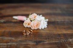 Boutonniere met ringen op de houten vloer stock afbeeldingen