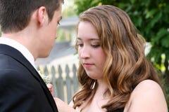 Boutonniere nervioso de la fijación de la muchacha del baile de fin de curso Fotografía de archivo