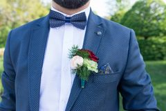 Boutonniere op het kostuumjasje van de bruidegom Modieuze bruidegom in matroos, wit overhemd en blauwe stropdas met boutonniere stock afbeeldingen