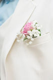 Boutonniere, pink rose on the white suit. Groom, wedding Stock Photo