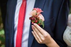 Boutonniere sur le marié à la mode au mariage Photographie stock libre de droits