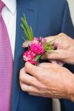 Boutonniere sur le marié à la mode au mariage Images stock