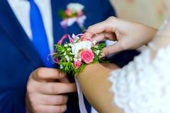Boutonniere sur une main de la jeune mariée Photo stock
