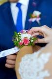 Boutonniere sur une main de la jeune mariée Photos libres de droits