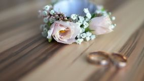 Boutonniere and wedding rings lie on a wooden Board stock video