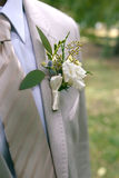 Boutonniere of white and yellow flowers with greens on lapel of a gray jacket. Close-up photo Royalty Free Stock Image